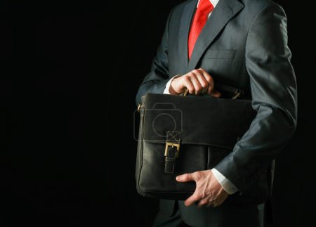 Photo for Portrait of successful business man with bag isolated on black background - Royalty Free Image