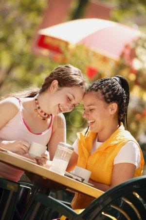 Photo pour Deux filles prennent un café au café - image libre de droit