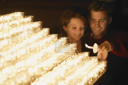 Photo for Young Couple Lighting A Candle - Royalty Free Image