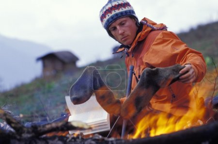 Man Drying Socks By Campfire