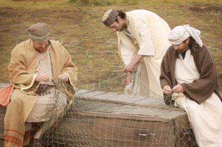 Three Men Working On A Fishing Net