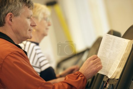 Man And Woman Reading On Stationary Bike