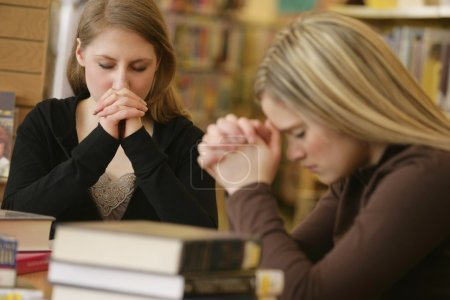 Two Women Praying In Library
