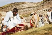 Dav sleduje, jak Ježíš pomáhá osoba ležící na zemi