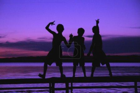 Photo pour Trois silhouettes des garçons sur un quai contre un coucher de soleil - image libre de droit