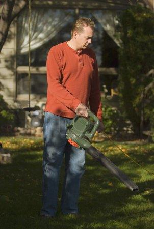 Photo pour Souffler des feuilles hors de la cour - image libre de droit