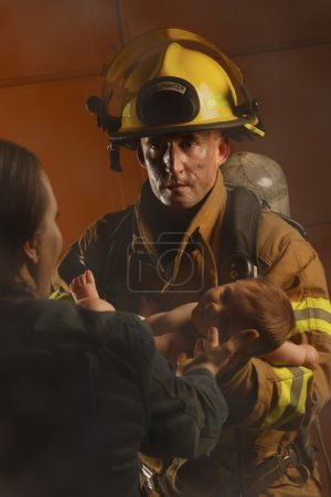 Fire Fighter Passing Baby To Mother...