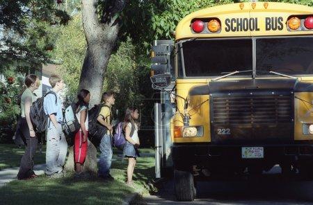Niños cargando un autobús escolar