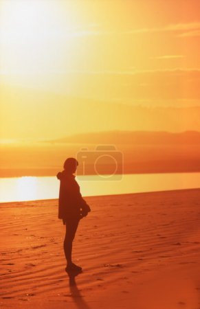 Photo for Silhouette Of Person Alone On Golden Beach - Royalty Free Image