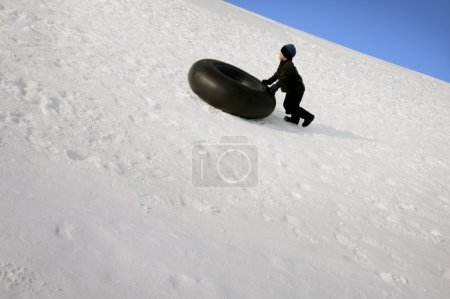 Boy Pushing Tube Uphill