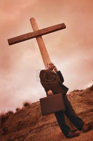 Photo pour Homme d'affaires sur le téléphone, s'appuyant sur une croix - image libre de droit