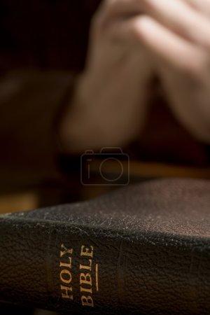 Closeup Of Bible With Praying Hands