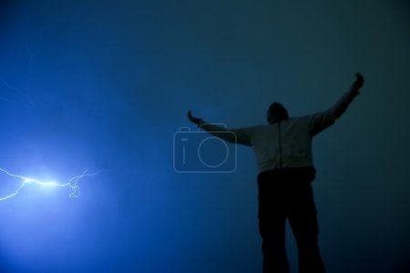 Photo for Man With Outstretched Arms In Lightning Storm - Royalty Free Image