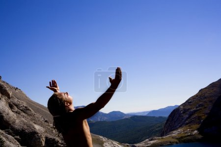 Young Man Worshipping On Mountain Top