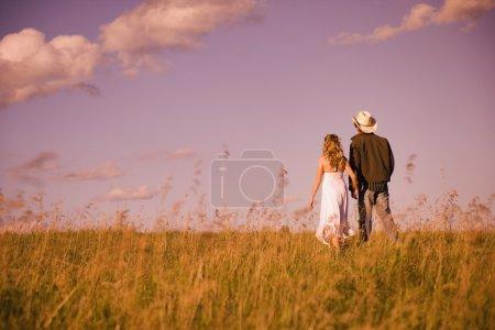 Photo pour Homme et femmes tenant la main et marchant sur le terrain - image libre de droit