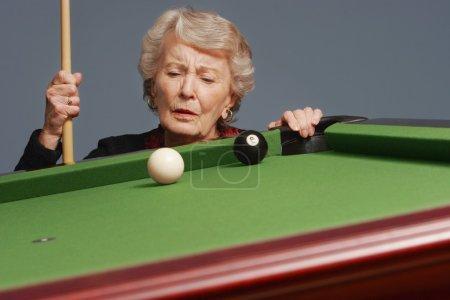 Senior Analyzing Pool Shot