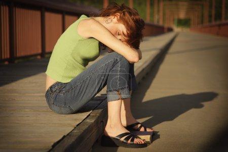 Woman Sits Down On A Bridge