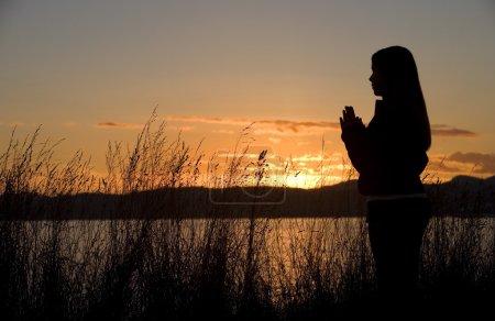 Photo pour Une adolescente prie au coucher du soleil près de l'océan . - image libre de droit