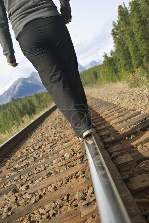 Photo pour Femme marchant sur les voies ferrées - image libre de droit