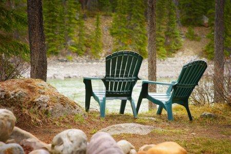 Photo pour Chaises de pelouse situées au bord du lac - image libre de droit