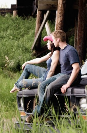 Couple Sitting On The Hood Of A Vehicle