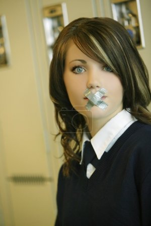 Female Student In Uniform With X Taped Over Mouth