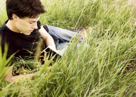 A Man Reading A Book In The Grass