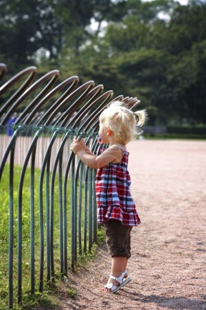 Girl Standing Against A Fence In A Park