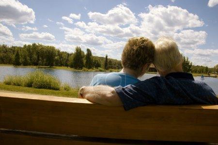couple marié assis sur un banc au bord du lac