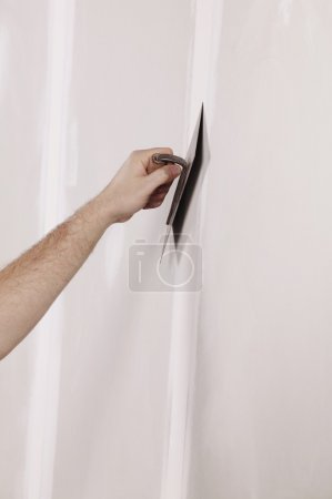 Man Using A Putty Knife On A Wall
