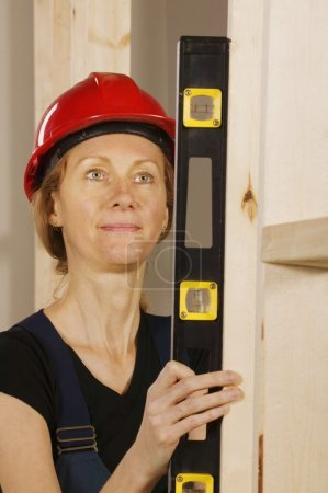 Female Construction Worker Using A Level