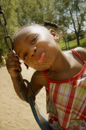 Young Girl Sticking Out Her Tongue While On The Swing Set At The Park