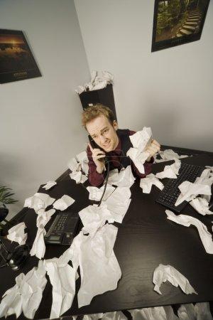 Photo pour Homme d'affaires au téléphone avec du papier éparpillé - image libre de droit