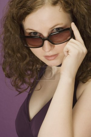 Photo for Brunette Woman Peering Over Sunglasses - Royalty Free Image