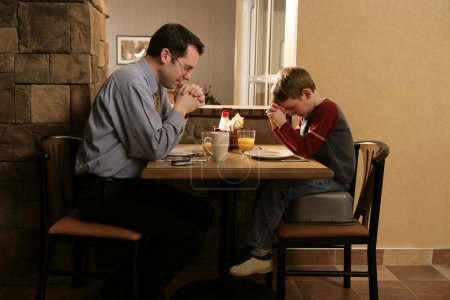 Father And Son Praying Before Meal