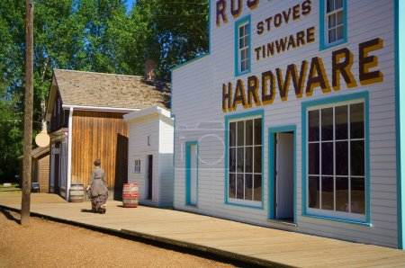 Woman In Period Dress Walking Past Historic Hardware Store At Fort Edmonton Park