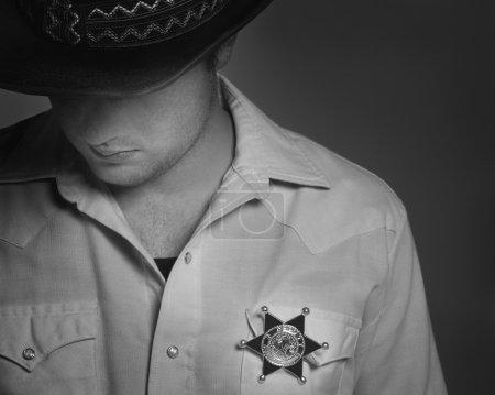 Photo pour Regardant vers le bas sous chapeau avec badge de shérif sur la chemise de cow-boy - image libre de droit