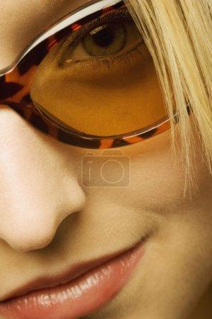 Photo pour Extrême gros plan de la femme portant des lunettes de soleil - image libre de droit
