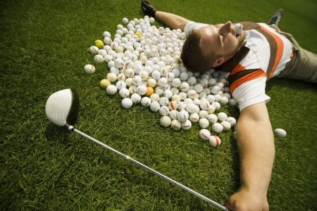 A Man Lying On Golf Balls