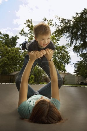 Mother Playing With Son On Trampoline