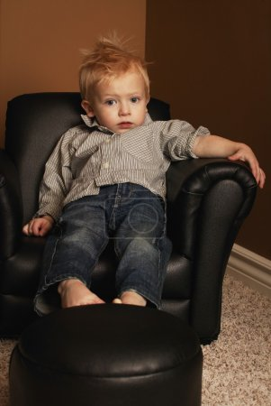 Photo for Boy Sitting In A Chair - Royalty Free Image