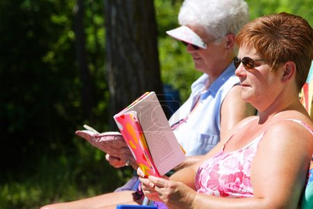 Two Woman Reading And Sunbathing