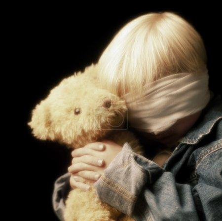 Boy With Bandage On Eyes And Holding Teddy Bear