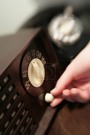 Woman Changing Dial On Old Radio