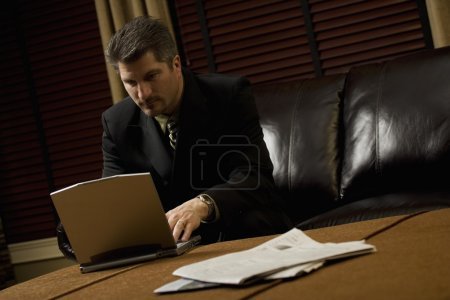 Businessman Working On His Laptop On The Coffee Table