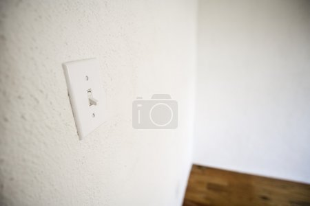 Empty Room With White Walls, White Lightswitch And A Wooden Floor