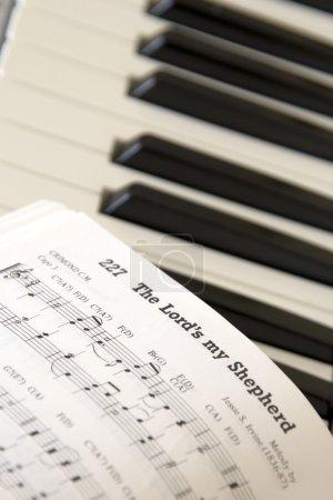 Photo pour Gros plan des feuilles de musique sur le clavier de piano - image libre de droit
