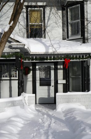 Christmas Decorations Hang Outside On A Snow Covered House