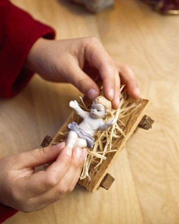 Child Playing With Figure Of Baby Jesus