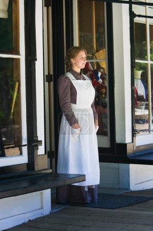Young Woman Standing In Store Doorway